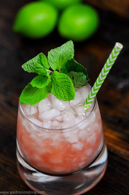 Pink cocktail in glass with green straw and mint