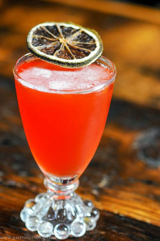 Pink cocktail in glass with citrus slice