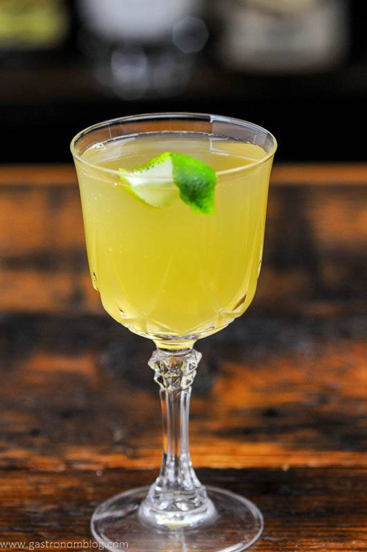 Yellow cocktail with lime peel