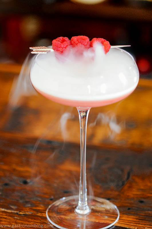 Pink cocktail in coupe with berries and dry ice