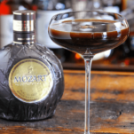 Brown cocktail in coupe, brown liqueur bottle in back