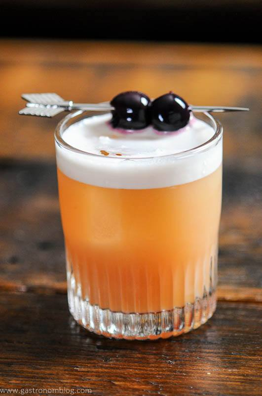 Peach colored cocktail with white foam, cherries