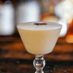 tan Rye whiskey sour in glass with star anise on foam