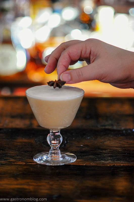 tan Cocktail in glass, start anise being placed on foam