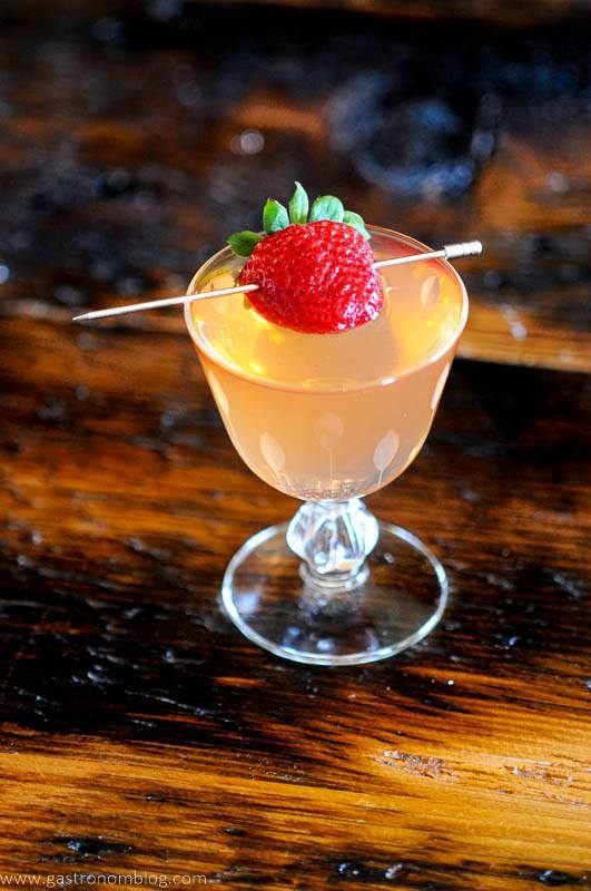 Strawberry on pick in glass cocktail, wood background