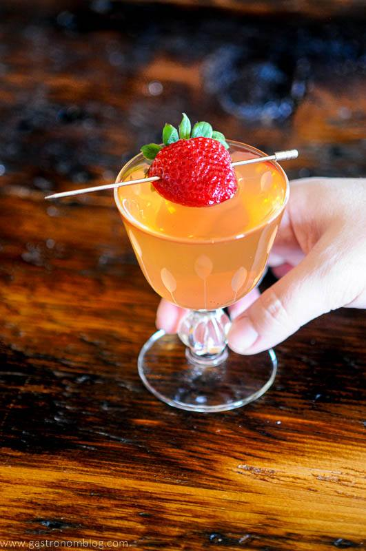 Pink cocktail in glass, strawberry on pick, hand holding glass