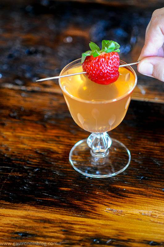Strawberry cocktail with berry on pick, hand holding pick