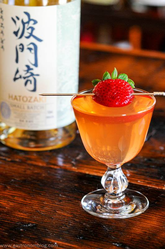 Pink cocktail with strawberry, Japanese whisky bottle