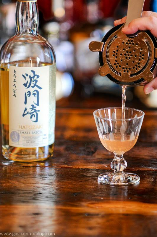 Pink cocktail being poured into glass, Japanese whisky bottle in background