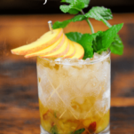 Peach Mint Julep Cocktail wtih peach slices and mint