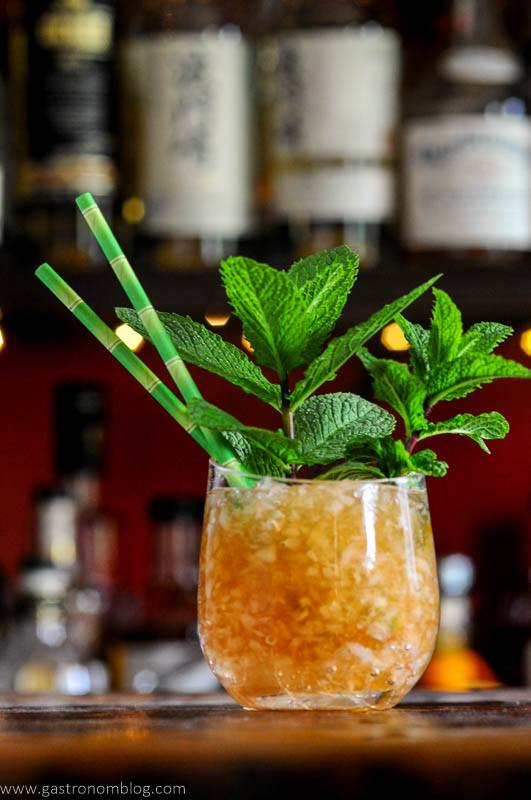 tan cocktail in glass with crushed ice, mint bunches and green straws