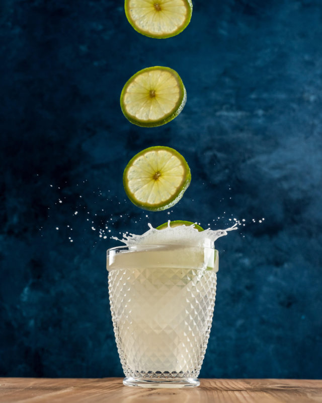 Limes being dropped in a margarita