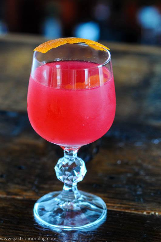 Pink cocktail with orange peel