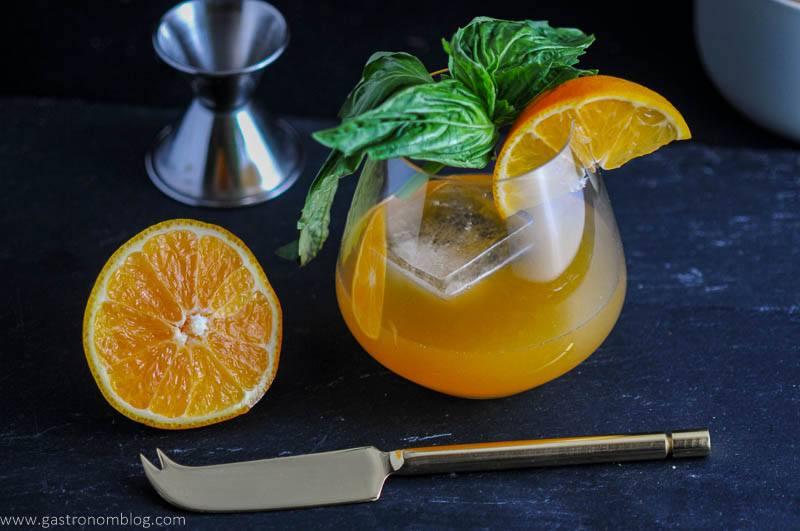 Orange cocktail, orange slice and basil in glass, orange sliced in half with knife and jigger on slate plate