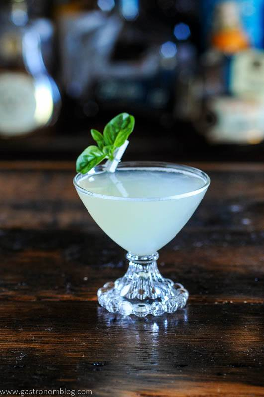 Basil gimlet in cocktail coupe with basil leaves