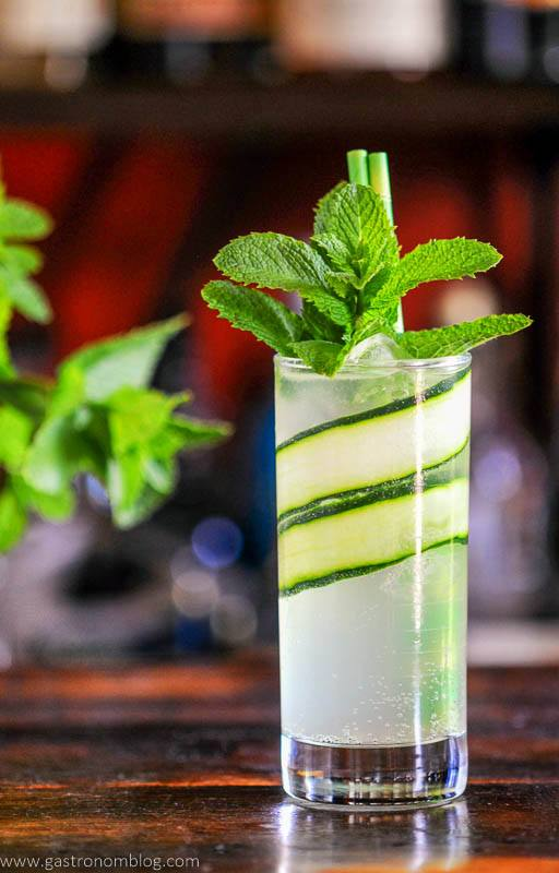 Tall glass cocktail lined with cucumber slices, mint garnish