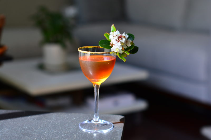 Tan cocktail in glass with white flower garnish