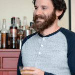 Man holding cocktail, in blue shirt, bar behind