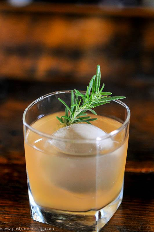 light orange cocktail in glass with ice and rosemary