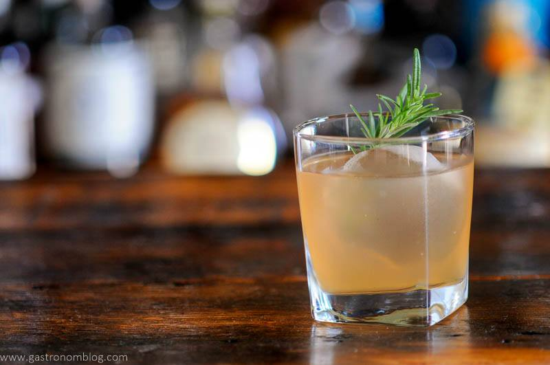 light orange cocktail in glass with ice and rosemary sprig