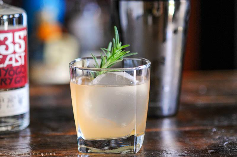 cocktail in glass with rosemary, shaker behind