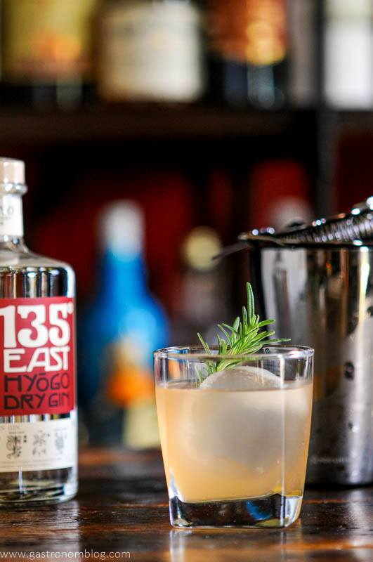 light orange cocktail in glass with rosemary, 135 East Gin bottle behind, strainer and shaker