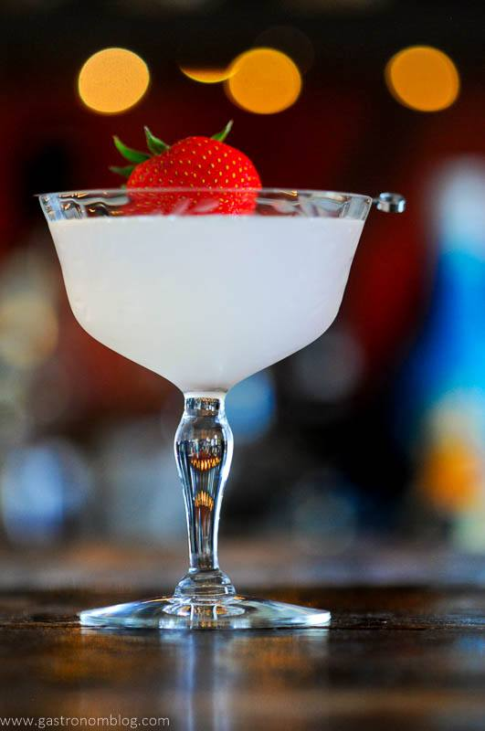 Opaque cocktail in coupe, strawberry on pick