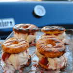 Glazed doughnut ice cream sandwiches on a cookie sheet outside
