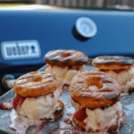 Grilled doughnuts with ice cream in between, on a cookie sheet outside