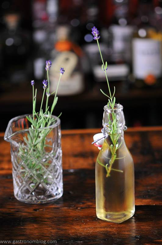 Lavender syrup in bottle, lavender sprigs in glass behind