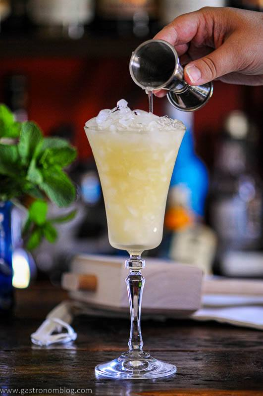 liquid being poured into tall cocktail glass with crushed ice