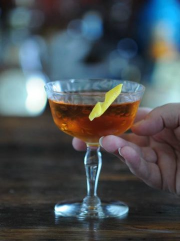 Brown cocktail in coupe with lemon peel