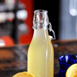 Yellow syrup in bottle with lemons