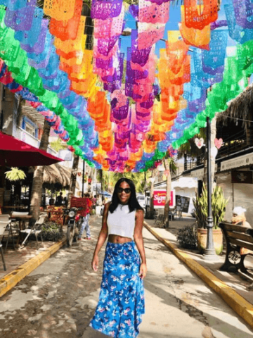 Woman walking under colorful flags
