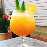 Pina Colada garnished with pineapple fronds on table outside