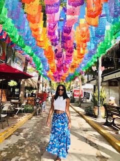 Lady in white top, blue skirt walks under rainbow colored lanterns in alleyway
