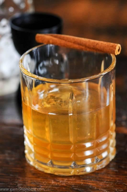 tan cockail in rocks glass with cinnamon stick garnish