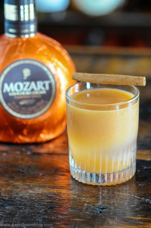 Orange cocktail in rocks glass, orange liqueur bottle behind