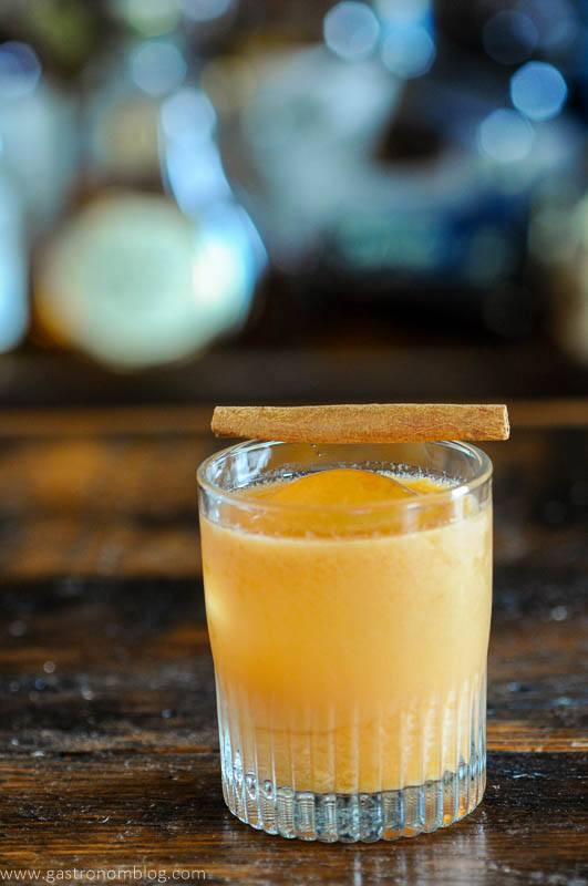 Orange pumpkin cocktail in rocks glass, cinnamon stick