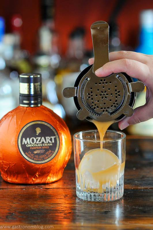 Orange Pumpkin cocktail being poured into a rocks glasses with clear ice ball, orange liqueur bottle behind
