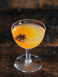 Scotch and apple cider cocktail in coupe with star anise garnish