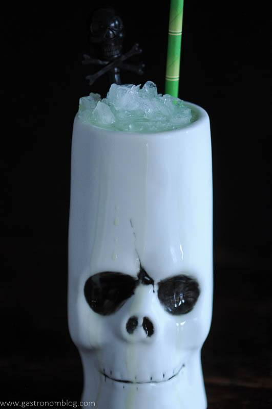 Skull tiki mug with green bamboo straw and skull pick
