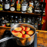 Citrus slices in wine in a saucepan on a burner