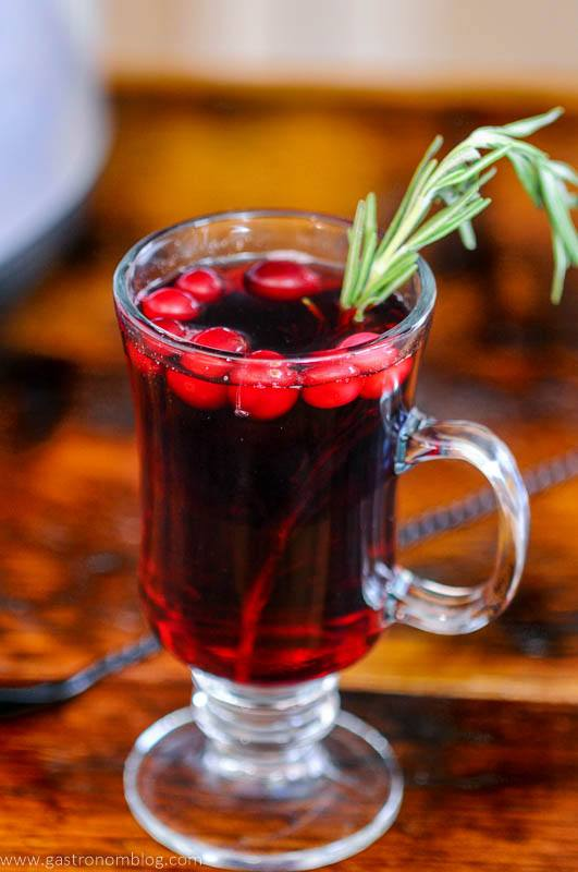 Red cocktail in mug with cranberries and rosemary