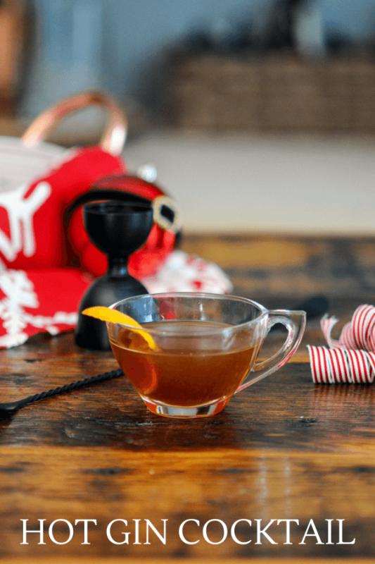 tan cocktail in a teacup, orange zest