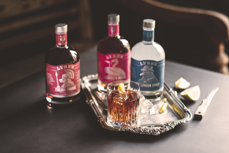 3 bottles on a tray with glass and garnishes