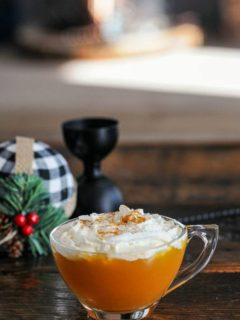 Orange cocktail in tea cup with whipped cream on top, christmas stuff behind
