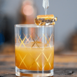 Gold etched glass with cocktail, tiny s'more on garnish pick