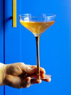 gin and champagne cocktail in coupe, blue background