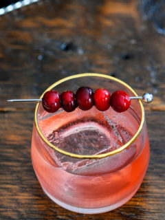 Top shot of cranberry mezcal cocktail with cranberries on a cocktail pick